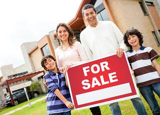 Happy family holding poster of a house for sale.jpeg