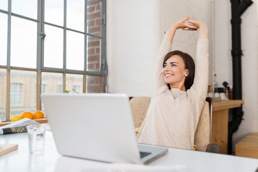 Happy relaxed young woman sitting in her kitchen with a laptop in front of her stretching her arms above her head and looking out of the window with a smile.jpeg